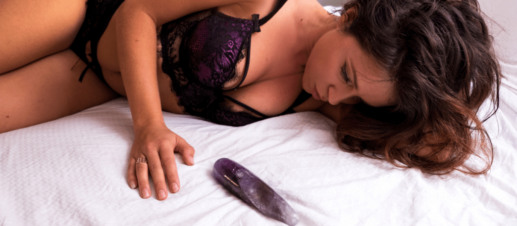 Beautiful woman satisfied with crystal dildo