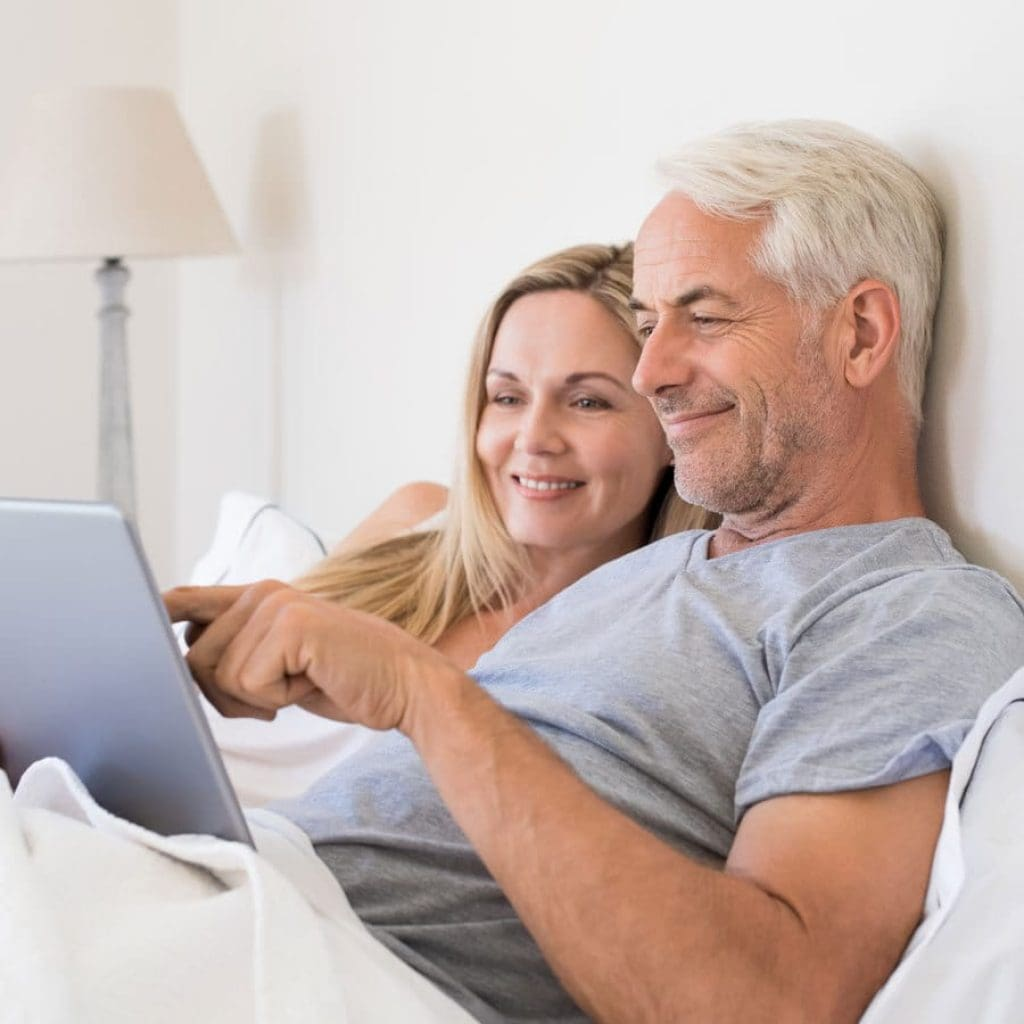 old couple in bed with laptop